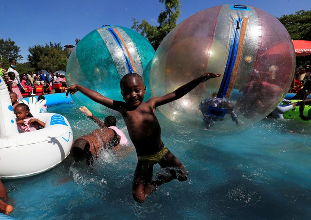 A child jumps in the portable swimming pool at the Uhuru Park grounds for Christmas Day celebrations in Nairobi, Kenya on December 25, 2020. (Photo by Thomas Mukoya/Reuters)