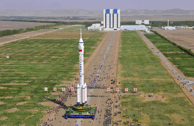 The Shenzhou 10 spacecraft, carried by a Long March-2F carrier rocket is moved into place at the launch pad in Jiuquan, Gansu province, on the morning of June 3, 2013. (Photo by STR/AFP Photo via The Atlantic)