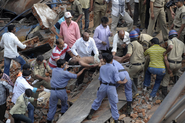 Indian rescue workers remove a body from the rubble at the site of the City Light Hotel building collapse in Secunderabad, the twin city of Hyderabad on July 8, 2013.  A two-storey hotel collapsed in the southern Indian city of Secunderabad on July 8, killing five restaurant workers and injuring 15 others, a local police official told AFP. (Photo by Noah Seelam/AFP Photo)