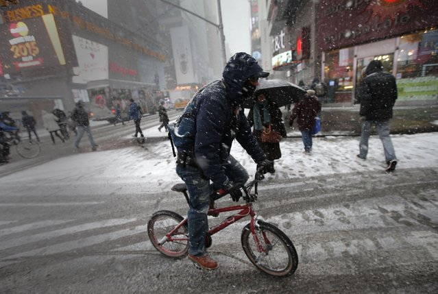 A man rides a bicycle through falling snow through Times Square in New York January 26, 2015. (Photo by Mike Segar/Reuters)