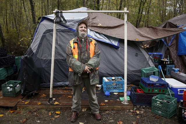 "Buzz Chevara, 56, poses in front of his tent at SHARE/WHEEL Tent City 4 outside Seattle, Washington October 9, 2015. ""The concept of tent city means community, safety and a place to be where nobody is going to harass or hurt you in the middle of the night"", Chevara said. (Photo by Shannon Stapleton/Reuters)"