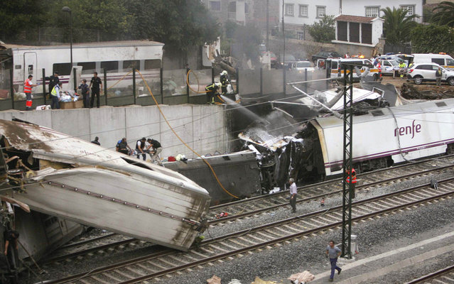 Emergency personnel respond to the scene of a train derailment in Santiago de Compostela, Spain, on Wednesday, July 24, 2013. (Photo by Antonio Hernandez/AP Photo/El correo Gallego)