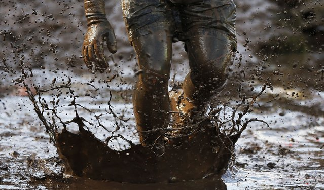 A competitor runs through mud during the Tough Guy event in Perton, central England, February 1, 2015. (Photo by Phil Noble/Reuters)