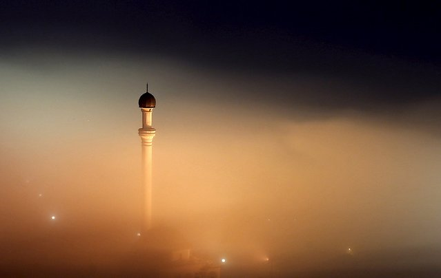 The minaret of a mosque is seen as smog blankets the village of Ponijeri, Bosnia and Herzegovina, December 26, 2015. With severe air pollution affecting the cities nestled among the mountains, the authorities have declared the first level of preparedness, advising the segment of the population that is at health risk to reduce movement in the mornings and evenings, appealing to drivers to use motor vehicles less and ordering heating utilities to lower the emission of harmful gases. (Photo by Dado Ruvic/Reuters)