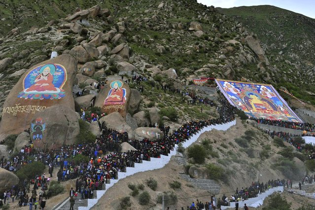 Tibetan Buddhists and tourists view a giant thangka during the Shoton Festival at Drepung Monastery in Lhasa, on August 6, 2013. (Photo by China Daily)