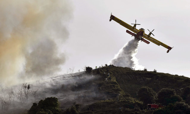 A firefighting aircraft during extinguishing works at Berango, northern Spain, 28 December 2015. The wind is making extinguishing works difficult as the fire, that started the previous day, continues burning and is getting close to houses in the town. (Photo by Miguel Tonya/EPA)