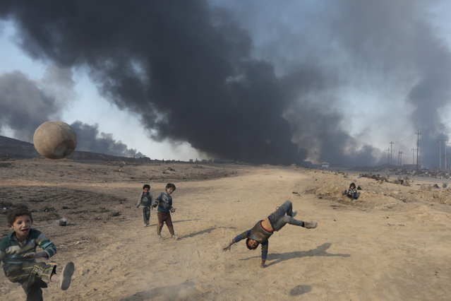 Boys play with a ball in front of oilfields burned by Islamic State fighters in Qayyara, south of Mosul, Iraq November 23, 2016. (Photo by Goran Tomasevic/Reuters)