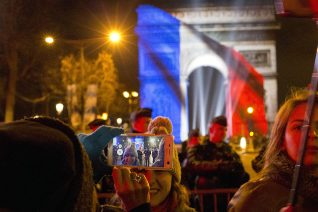 Revellers take souvenir selfies at the end of  the 5-minute video performance displayed on the Arc de Triomphe as part of New Year's Eve celebrations on the Champs Elysees Avenue in Paris, France, Friday, January 1, 2016. (Photo by Francois Mori/AP Photo)