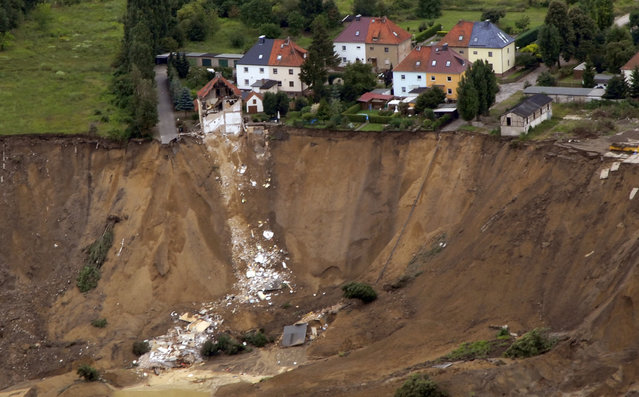 An aerial view shows the debris of a residential building and a destroyed road in the village of Nachterstedt, July 18, 2009. Three residents were missing in the eastern German village of Nachterstedt after their lakeside home and another building suddenly collapsed early Saturday into the water. A 350-metre stretch of shoreline gave way next to an old open-cast coalmine converted to a lake, about 170 kilometres south-west of Berlin. (Photo by Reuters/Gemeindeverwaltung Nachterstedt)