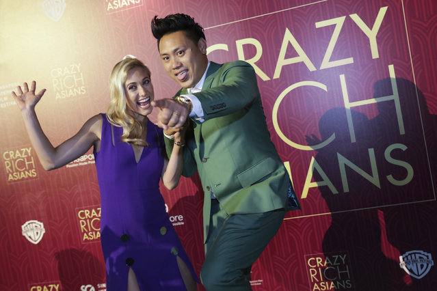 """Director John Chu and his wife Kristin Hodge pose for photographers as they arrive for the red carpet screening of the movie """"Crazy Rich Asians"""" on Tuesday, August 21, 2018, in Singapore. (Photo by Don Wong/AP Photo)"""