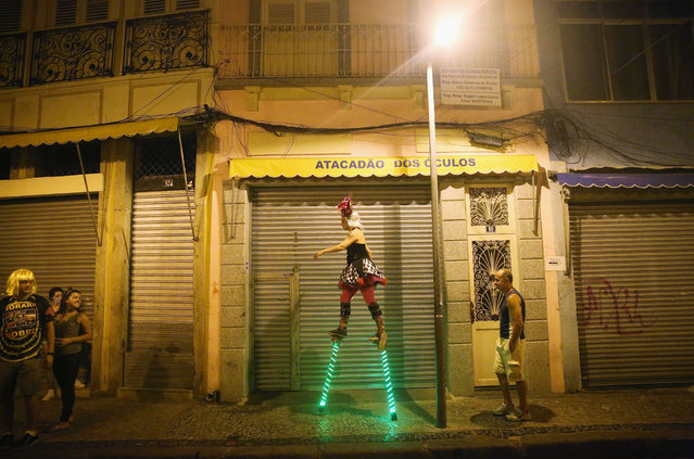 """A stilt-walker strides towards revelers during the My Light is LED """"bloco"""" pre-Carnival street parade on February 12, 2015 in Rio de Janeiro, Brazil. Carnival runs this year February 13-17. (Photo by Mario Tama/Getty Images)"""