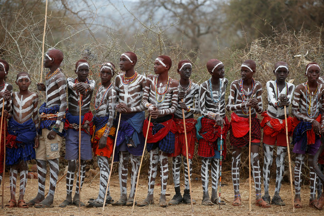 Maasai children part of the leaders' group stand during an initiation into an age group ceremony near the town of Bisil, Kajiado county, Kenya on August 23, 2018. Thousands of Kenyan boys had a blessing of milk and beer sprayed on them as part of a rare Maasai ethnic community initiation ceremony to mark their passing into early manhood. (Photo by Baz Ratner/Reuters)