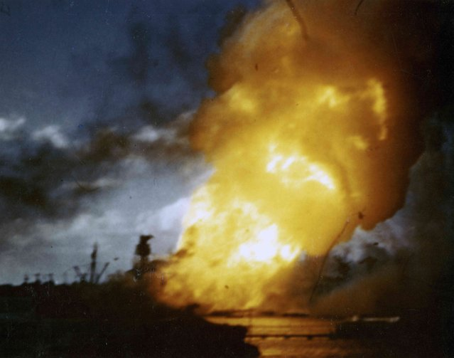 The battleship USS Arizona burns, immediately following the explosion of her forward magazines, during the Japanese attack on Pearl Harbor, Hawaii, U.S. December 7, 1941. The still image is from a color motion picture taken on board the hospital ship USS Solace. (Photo by Eric Haakenson/Reuters/U.S. Navy/National Archives)