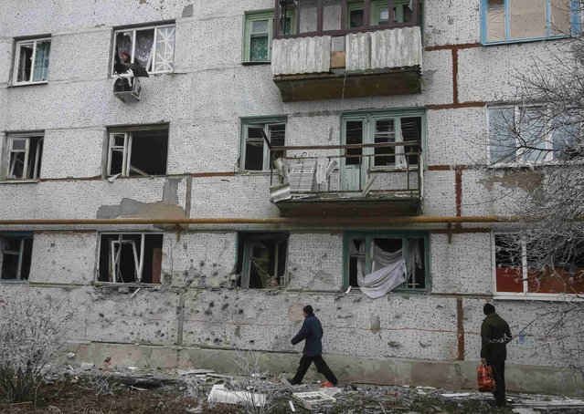 Local residents pass near by their house after shelling in recent days in Svitlodarsk, eastern Ukraine, February 15, 2015. (Photo by Gleb Garanich/Reuters)