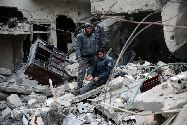 Civil defence members rest amidst rubble in a site hit by what activists said were airstrikes carried out by the Russian air force in the town of Douma, eastern Ghouta in Damascus, Syria January 10, 2016. (Photo by Bassam Khabieh/Reuters)