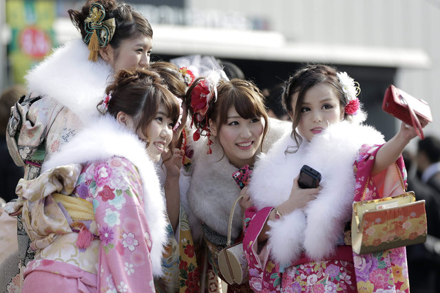 Young Japanese women dressed in colourful Kimonos take a photo of themselves as they gather for a ceremony marking the 'Coming of Age Day' at the Toshimaen Amusement Park in Tokyo, Japan, 11 January 2016. The Coming of Age Day is the day to celebrate young people who turn 20 years old while the age of 20 is considered the beginning of adulthood and is the minimum legal age for voting, drinking and smoking in Japan. (Photo by Kiyoshi Ota/EPA)