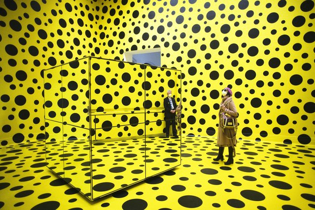 """People walk through the art work """"THE SPIRITS OF THE PUMPKINS DESCENDED INTO THE HEAVENS"""" by Yayoi Kusama, during the press preview of a retrospective exhibition of the Japanese artist at the Martin Gropius Bau museum in Berlin, Germany, Thursday, April 22, 2021. (Photo by Markus Schreiber/AP Photo)"""