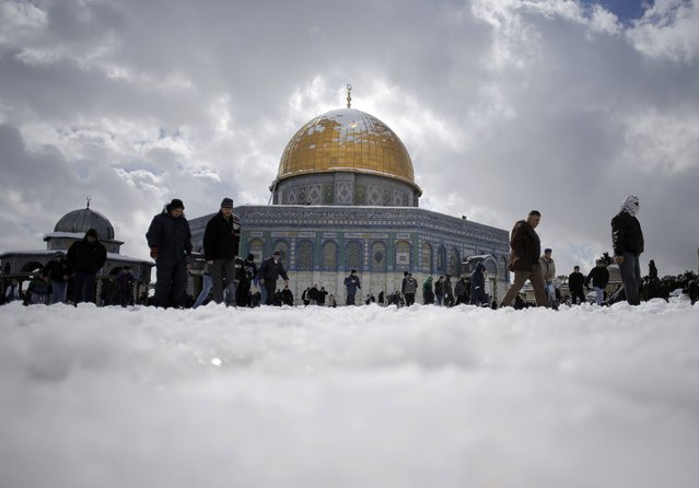 Palestinian walk in front of the snow-covered Dome of the Rock on the compound known to Muslims as Noble Sanctuary and to Jews as Temple Mount, ahead of Friday prayers in Jerusalem's Old City February 20, 2015. (Photo by Ammar Awad/Reuters)