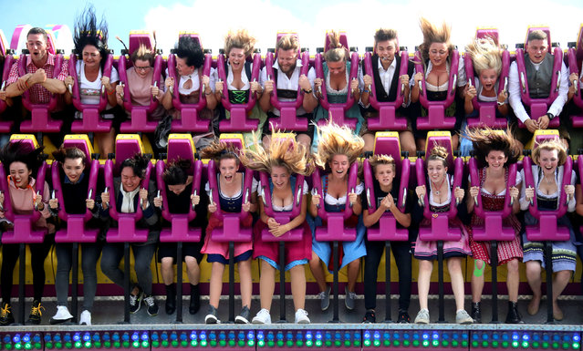 Visitors ride a roller coaster during the opening day of the 185th Oktoberfest in Munich, Germany September 22, 2018. (Photo by Michael Dalder/Reuters)