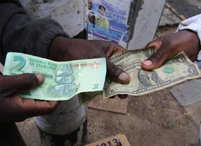 Illegal money changers pose while exchanging a new Zimbabwe bond note (L) and U.S. dollar notes in the capital Harare, Zimbabwe, November 28, 2016. (Photo by Philimon Bulawayo/Reuters)