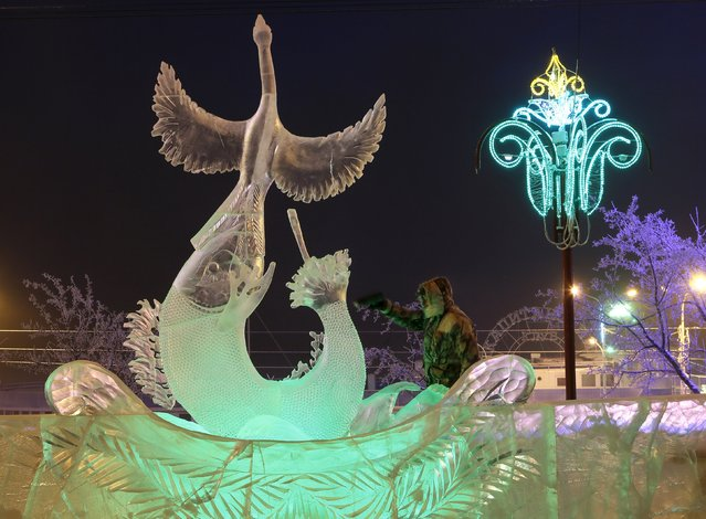 "Mikhail Vasilenko, a participant from the Siberian town of Nizhny Tagil, works on an ice sculpture called ""The Predator"", on the last day of the annual international festival of snow and ice sculptures ""The Magical Ice of Siberia"", with the air temperature at about minus 28 degrees Celsius (minus 18.4 degrees Fahrenheit), in Krasnoyarsk, Russia, January 17, 2016. (Photo by Ilya Naymushin/Reuters)"