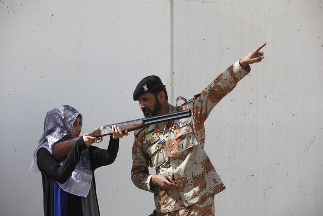 Pakistan Rangers soldier gestures as he instructs a female student of Nadirshaw Eduljee Dinshaw (NED) University during a counter-terrorism training demonstration at the Rangers Shooting & Saddle Club (RSSC) on the outskirts of Karachi, February 24, 2015. More than 200 students of NED University have visited RSSC to observe the counter-terrorism training demonstration, Sachal Rangers official Khalid Goraya said. (Photo by Akhtar Soomro/Reuters)