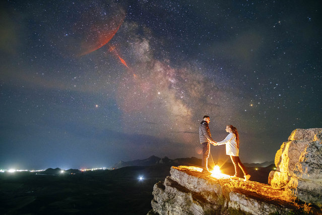 "These images show a heart-warming moment between a loving couple as they're lit up under a stunning starry night sky. Taken on the Crimean Peninsula, the images show couples posed up beneath a glorious midnight skyscape. Photographer Andrei Sheliakin, 29, said: ""I have to take the shots at night so it makes the shoot more difficult both for me and for the couples. Usually though, they're up for anything to get the shots like these. Of course, in summer everything is easier and more comfortable"". (Photo by Andrei Sheliakin/Caters News Agency)"