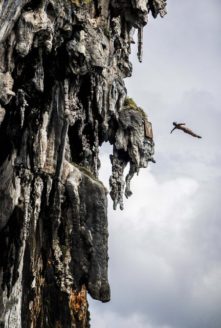 In this handout image provided by Red Bull, Orlando Duque of Colombia dives from a 25 metre rock at Viking Caves in the Andaman Sea during competition on the fifth day of the final stop of the 2013 Red Bull Cliff Diving World Series on October 24, 2013 at Phi Phi Island, Thailand. (Photo by Dean Treml/Red Bull via Getty Images)