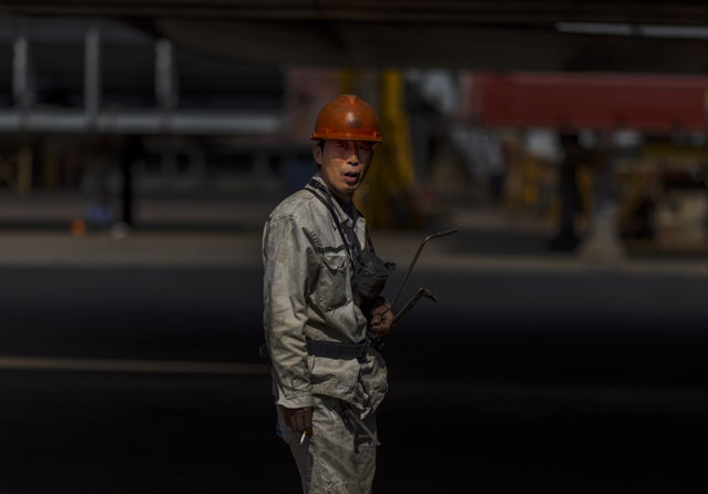 A workers walks in the Yangzijiang Shipbuilding Group shipyard, a privately owned large-scale enterprise integrating shipbuilding and marine engineering manufacturing in Jiangyin, Jiangsu province, China, 18 October 2018. The company is second biggest in the world for cargo ships after South Korea, by ship orders and numbers of ships made during one year. China's economy grew slower than expected at 6.5 percent year-over-year in the quarter that ended in September, according to data announced by the National Bureau of Statistics on 19 October 2018. The latest Gross Domestic Product (GDP) figures missed expectations, indicating the the world's second largest economy is feeling the impact of its trade war with the US. (Photo by Aleksandar Plavevski/EPA/EFE)