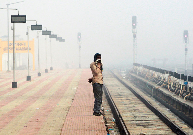A man waits for a train at a railway platform on a foggy winter morning, on the outskirts of Agartala, India, December 13, 2016. (Photo by Jayanta Dey/Reuters)