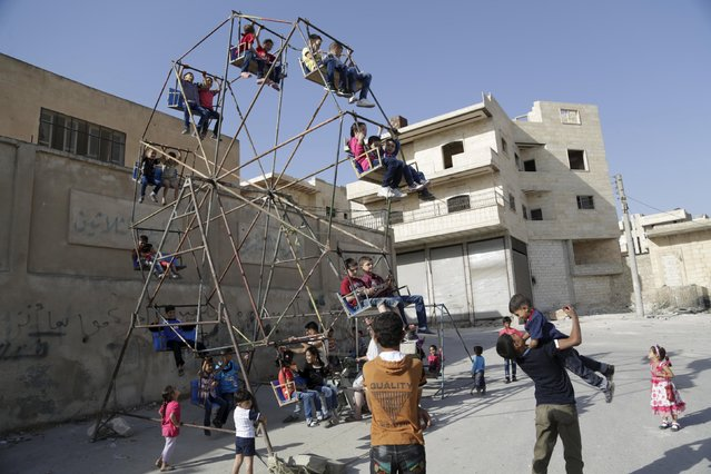 Children play on swings on the first day of Eid al-Adha in Maaret al-Naaman town in Idlib province, Syria September 24, 2015. (Photo by Khalil Ashawi/Reuters)