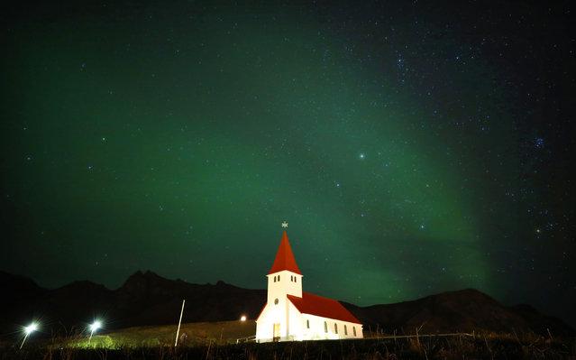 The northern lights glow above a church in Reyniskirkja, Vík, Iceland on December 4, 2018. (Photo by Owen Humphreys/PA Wire Press Association)