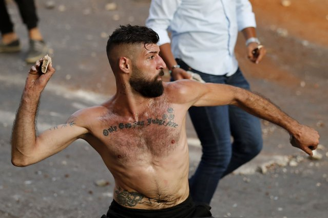 """A supporter of Prime Minister-designate Saad Hariri who stepped down on Thursday, throws stones against Lebanese soldiers during a clash, in Beirut, Lebanon, Thursday, July 15, 2021. Hariri says he is stepping down, nine months after he was named to the post by the parliament. He is citing """"key differences"""" with the country's president, Michel Aoun. (Photo by Hussein Malla/AP Photo)"""