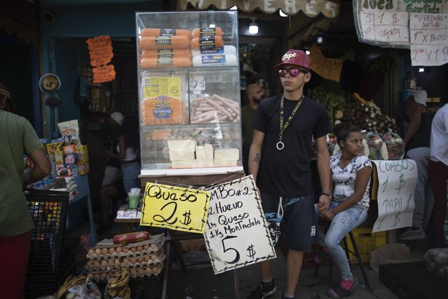 Signs promoting cheese, eggs and mortadella are displayed in a market in Caracas, Venezuela, Friday, June 11, 2021. (Photo by Ariana Cubillos/AP Photo)