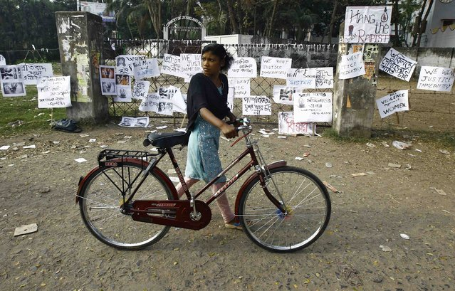 A woman pushes her bicycle past a gate with various messages tied to it outside the Convent of Jesus and Mary school in Ranaghat in the eastern Indian state of West Bengal March 18, 2015. In the days before the rape of an elderly nun in an armed assault that has shaken India, death threats and extortion attempts had already shattered the peace at her Convent of Jesus and Mary school, police and school officials say. (Photo by Rupak De Chowdhuri/Reuters)