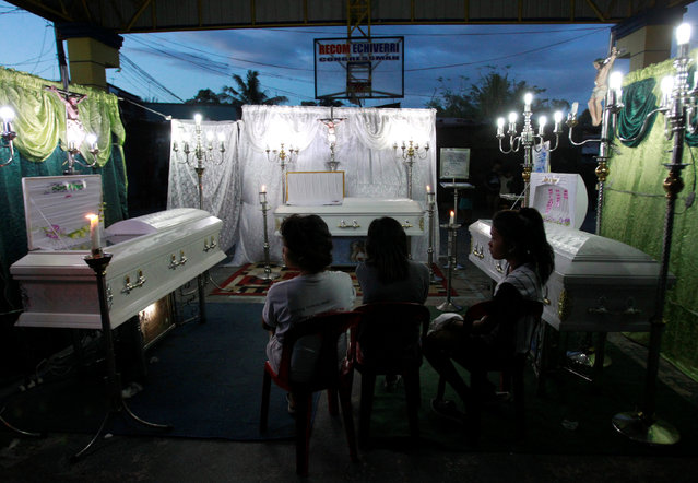 Grieving relatives attend the wake of Analyn Diamla, 22 (L), Ednel Santor, 22 (C) and Kristine Santor, 44 (R), who according to police were killed by unidentified gunmen at a drug den, in Caloocan city, Metro Manila, Philippines, December 30, 2016. (Photo by Czar Dancel/Reuters)