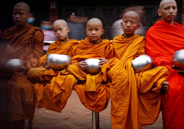 Buddhist monks wait to receive alms during the birth anniversary of Buddha, also known as Vesak Day, at Boudhanath Stupa in Kathmandu, Nepal, April 30, 2018. (Photo by Navesh Chitrakar/Reuters)