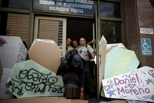 A woman moves cardboard coffins blocking the door of the  LA County Board of Supervisors' office as she tries to exit after a march to commemorate the more than 617 people they say have been killed by law enforcement in LA County since 2000, in Los Angeles, California April 7, 2015. (Photo by Lucy Nicholson/Reuters)