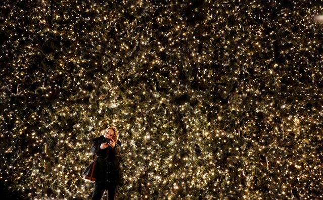 A woman takes a picture of herself with part of the Christmas illumination at a shopping mall in Berlin. (Photo by Fabrizio Bensch/Reuters)