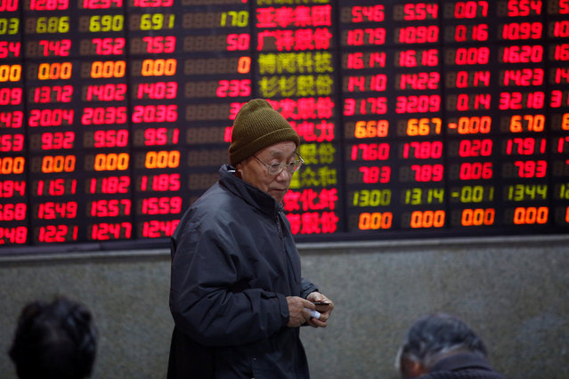 An investor walks in front of an electronic board showing stock information on the first trading day after the New Year holiday at a brokerage house in Shanghai, China, January 3, 2017. (Photo by Aly Song/Reuters)