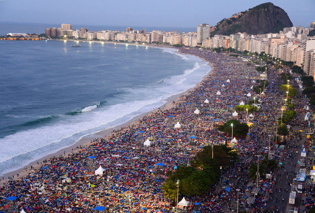 Catholic pilgrims attending World Youth Day (WYD) crowd Copacabana beach in Rio de Janeiro on July 28, 2013 after spending the night sleeping here following a prayer vigil headed by Pope Francis. (Photo by Vanderlei Almeida/AFP Photo)