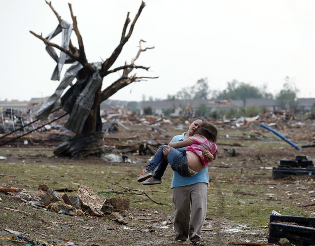 A woman carries her child through a field near the collapsed Plaza Towers Elementary School in Moore, Okla., Monday, May 20, 2013. A tornado as much as a mile (1.6 kilometers) wide with winds up to 200 mph (320 kph) roared through the Oklahoma City suburbs Monday, flattening entire neighborhoods, setting buildings on fire and landing a direct blow on an elementary school. (Photo by Sue Ogrocki/AP Photo)