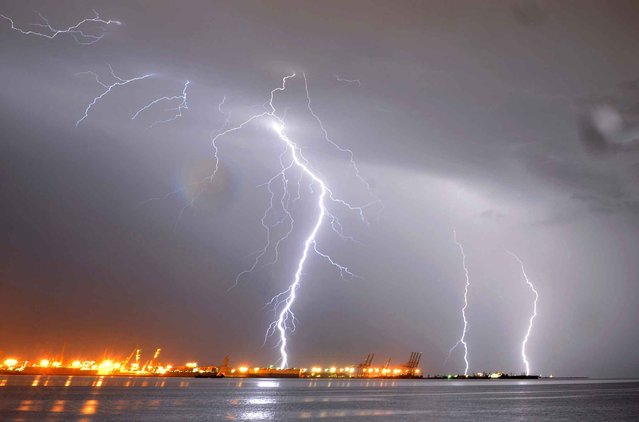 Lightning streaks over the port of Montevideo during a thunderstorm early on January 2, 2014. (Photo by Mariana Suarez/AFP Photo)