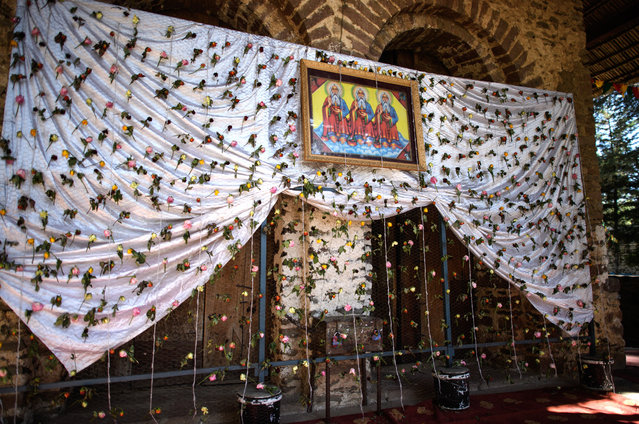 A picture depicting the Three Kings is displayed on cloth decorated with flowers on Debre Birhan Selassie Church ahead of the annual Timkat celebration, on January 17, 2017 in Gondar, Ethiopia. (Photo by Carl Court/Getty Images)