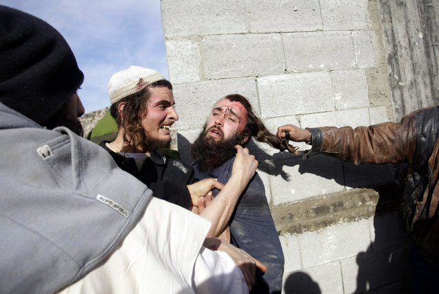 Palestinians hit injured Israeli settlers, center, detained by Palestinian villagers in a building under construction near the West Bank village of Qusra, southeast of the city of Nablus, Tuesday, January 7, 2014. (Photo by Nasser Ishtayeh/AP Photo)