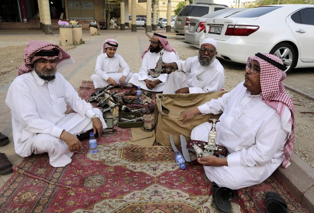 In this April 16, 2015 photo, dagger vendors sit together, one of them reciting poetry about traditional Saudi daggers, at al-Aqeeliya open-air auction market, in Riyadh, Saudi Arabia. Souvenir swords that sell as decorative pieces can go for more than 40 Saudi riyals ($10) in one of the market's stalls, but at the auction a whole bundle of 10 or more sells for 100 riyals ($27) to the highest bidder. (Photo by Hasan Jamali/AP Photo)