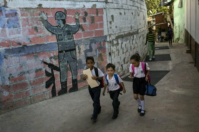 In this February 1, 2019 photo, children walk past a mural that depicts the surrender of a U.S. soldier, in Caracas, Venezuela. Caritas, a charity run by the Roman Catholic church, estimates that child malnutrition more than doubled last year in Venezuela due to widespread food shortages and 7-digit hyperinflation, while 48 percent of pregnant women in low-income neighborhoods are also underfed. (Photo by Rodrigo Abd/AP Photo)