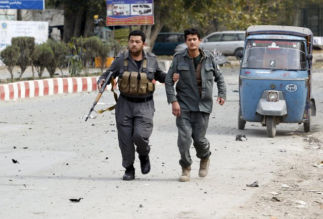 An Afghan policeman helps his wounded comrade during gunfire near the Indian consulate in Jalalabad, Afghanistan March 2, 2016. (Photo by Reuters/Parwiz)