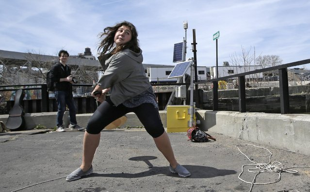 Women's division winner 18-year-old Nada Zimmermann of Innsbruck, Austria, prepares to hurl a banjo into a heavily polluted New York waterway during the fifth annual Brooklyn Folk Festival's Gowanus Banjo Toss, Sunday, April 19, 2015, in the Brooklyn borough of New York. Zimmermann won a new banjo for throwing the instrument a record-setting 67-feet. (Photo by Kathy Willens/AP Photo)