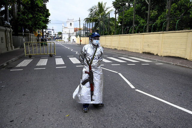 A policeman stands guard along a street during a nationwide 10-day lockdown imposed to curb the spread of Covid-19 coronavirus in Colombo on August 21, 2021. (Photo by Ishara S. Kodikara/AFP Photo)